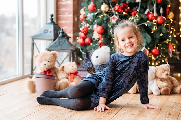 Christmas fun. happy little girl sitting on floor, smiling. blur window, decorated fir tree and teddy bears