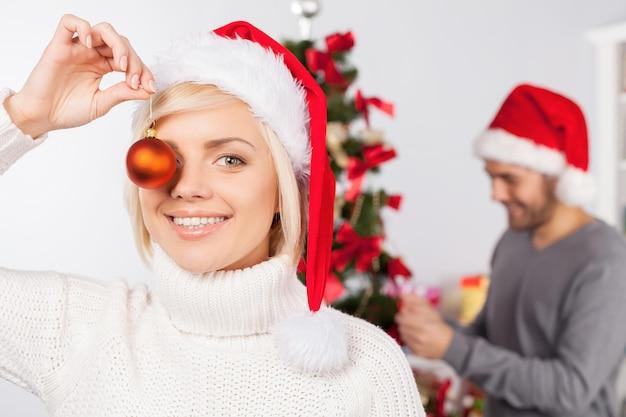 크리스마스 재미. 그녀의 남자 친구가 배경에 크리스마스 트리를 장식하는 동안 장난 젊은 여자