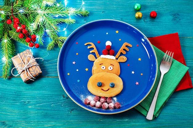 子供のためのクリスマスの面白い食事、お祭りの装飾が施された青いプレート上のトナカイのパンケーキ。