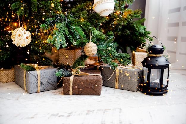 Christmas fur tree with toys and presents. christmas lights bokeh horizontal view copyspace