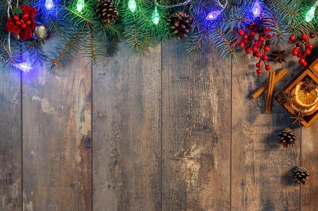 クリスマスの花輪のライトと木製の背景の装飾。ダークボードのクリスマスデコレーション
