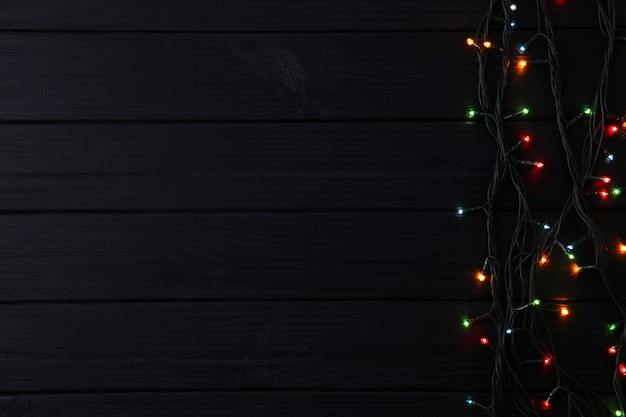 Christmas garland lights on black background, copy space