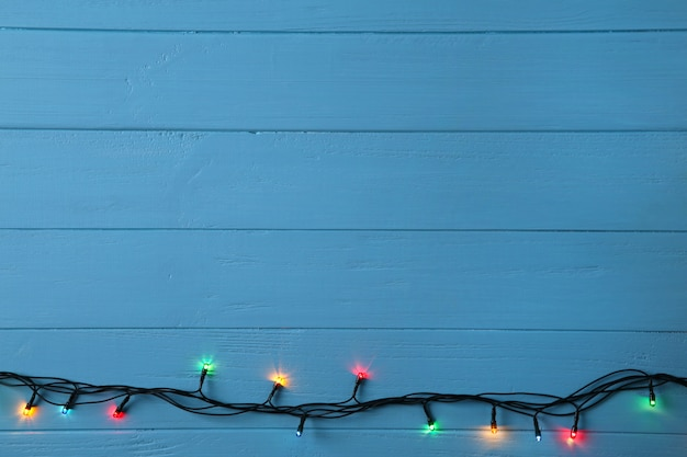 Christmas garland lights on blue background, copy space