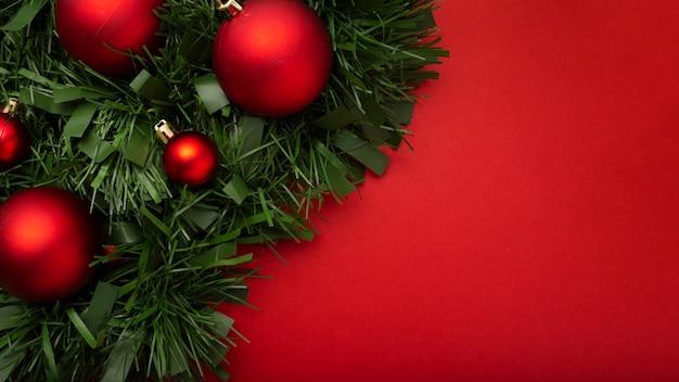 Ghirlanda di natale fatta di foglie e palline su un tavolo rosso