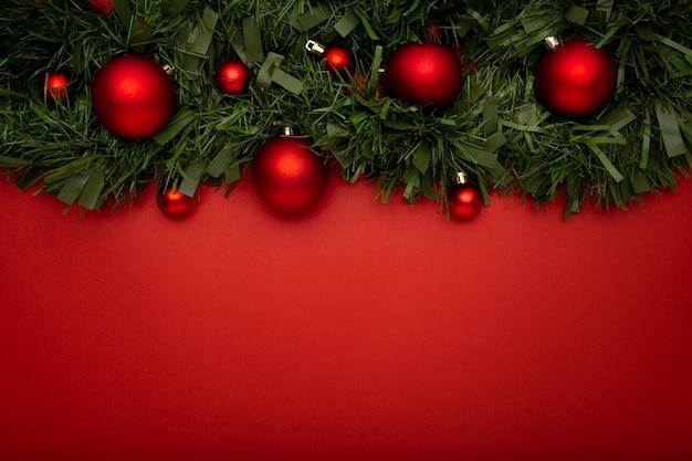 赤いテーブルの上に葉とボールで作られたクリスマスの花輪
