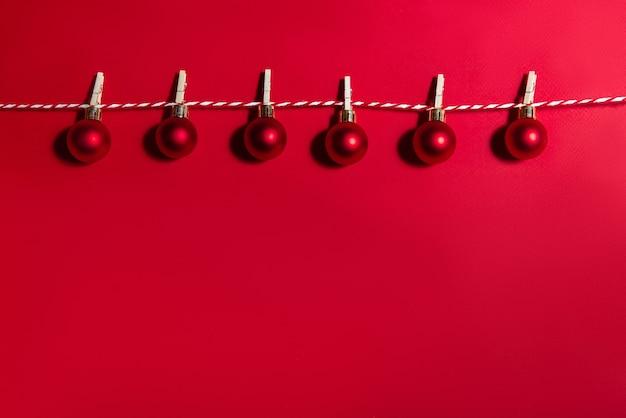 빨간색 배경에 스레드에 매달려 공의 크리스마스 화환. 새해 개념