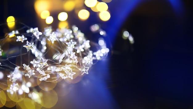 유리 병의 크리스마스 화환, 내부에 식물이 있는 항아리. 새 해와 크리스마스 개념입니다. 아름다운 빛과 보케가 있는 전구 화환