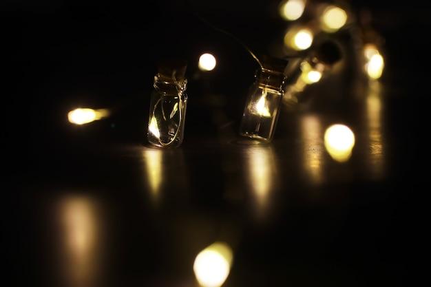 ガラス瓶のクリスマスの花輪、中に植物が入った瓶。新年とクリスマスのコンセプト。美しい光とボケ味のある電球の花輪