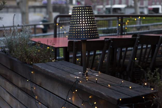 テラスのクリスマスの花輪。イブニングランプが木製のインテリアを照らします。