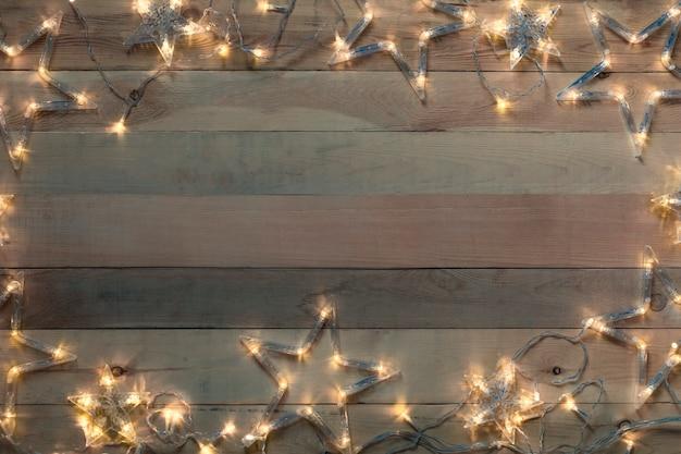 木製の古い背景に輝くクリスマスガーランドスター。コピースペース、フラットレイアウト