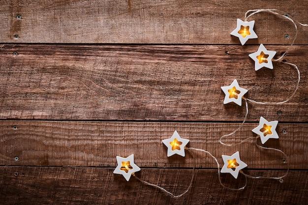 오래 된 어두운 나무 배경에 나무 빛 별 크리스마스 화 환. 복사 공간이 있는 상위 뷰입니다. 크리스마스 인사말 카드입니다.
