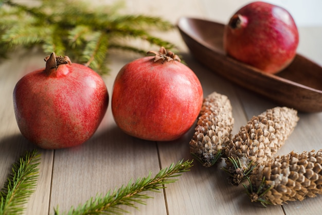 Christmas garnet fruit, spruce tree branch, big bumps on a textured background