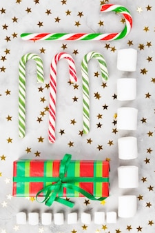 Christmas geometric composition. gifts, caramel canes, marshmellows on gray concrete background with sparkling stars.