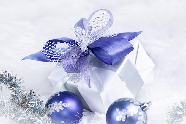 お祝いの白のクリスマスプレゼントと青いクリスマスボール。