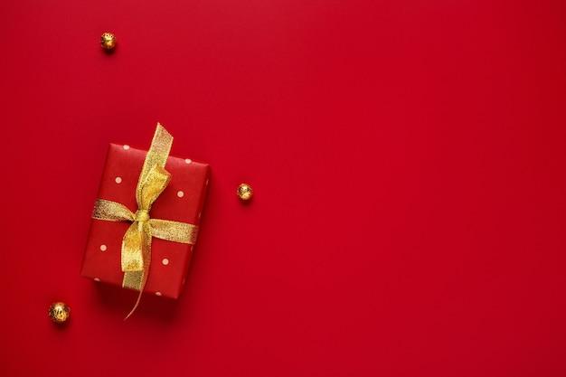 コピースペースと赤の背景にクリスマスプレゼントとゴールドの装飾。