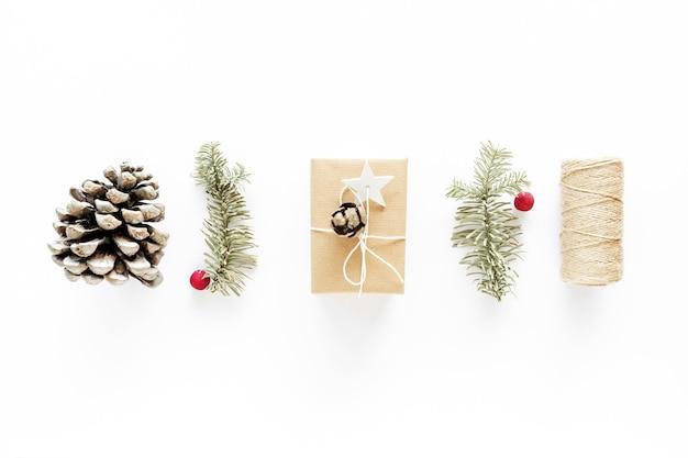 白い表面のクリスマスプレゼントアート構成。ギフト、クリスマスの木製装飾、モミの枝、松ぼっくり。手作りのdiyコンセプト。フラットレイ、上面図。冬のフラットレイ休日の背景