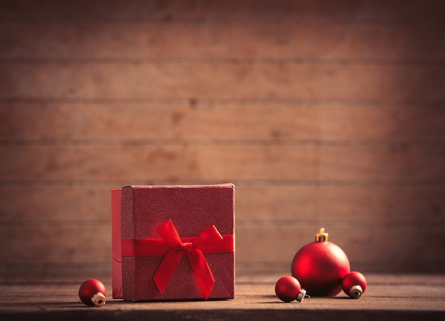 Christmas gift and baubles on wooden table and background