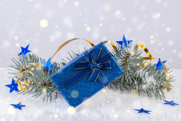 明るい背景に青い星とトウヒの枝の近くのクリスマスプレゼントの青いボックス