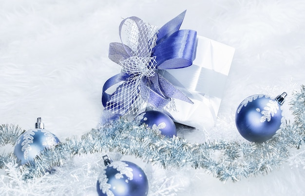 Christmas gift and blue christmas balls on a festive white background .photo with copy space