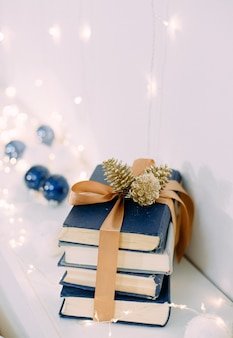 Christmas gift books with ribbons and garlands magic
