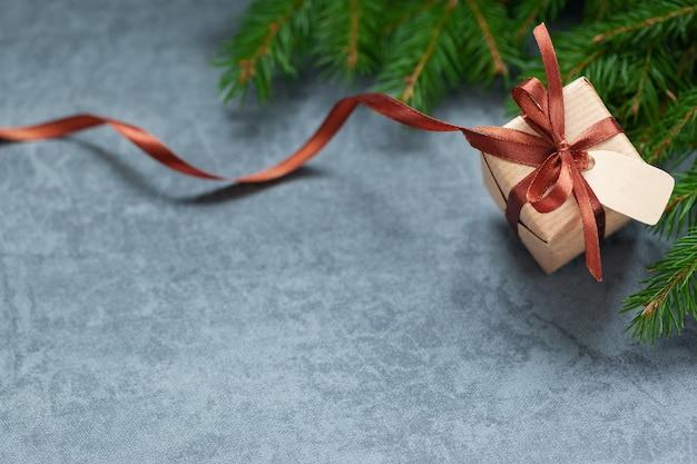 クリスマスギフトボックスとダークグレーのタグが付いた茶色のリボン