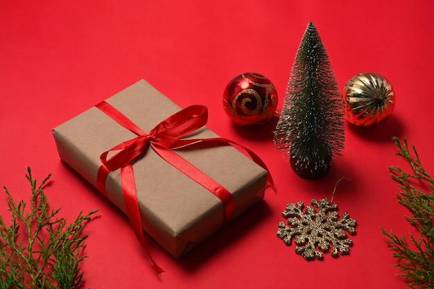 赤い背景の上のクリスマスギフトボックスとクリスマスの装飾品