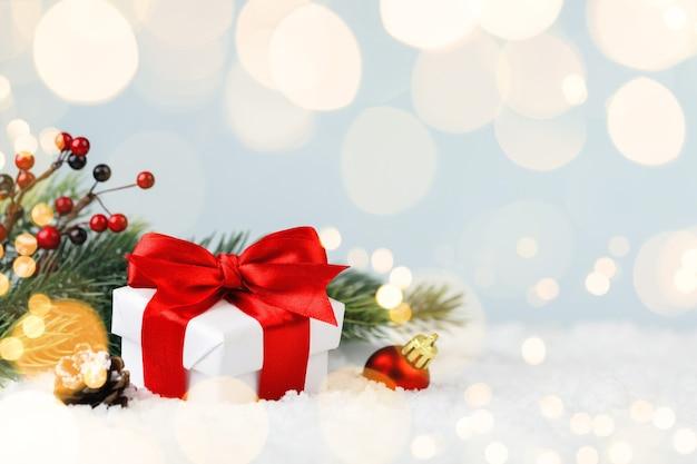 雪の吹きだまりのクリスマスギフトボックスとモミの木