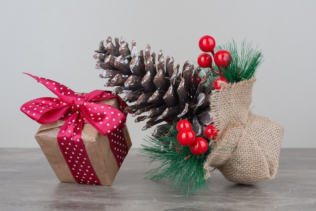 Рождественская подарочная коробка и шишка на мраморном столе.