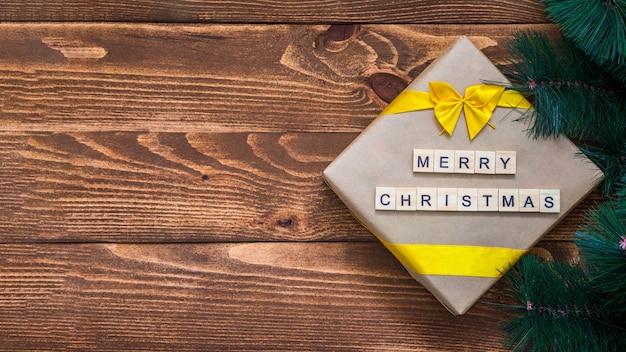 メリークリスマスのテキストと木製の背景にクリスマスギフトボックスと木の枝の装飾。グリーティングカード。フラットレイ。コピースペースのある上面図。新年のコンセプト。休日とおめでとうございます。