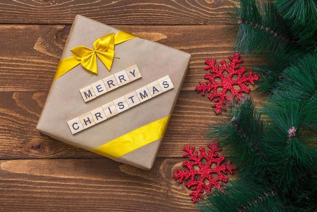 メリークリスマスのテキストと木製のテーブルの上のクリスマスギフトボックスと木の枝の装飾。グリーティングカード。フラットレイ。上面図。新年のコンセプト。休日とおめでとうございます。