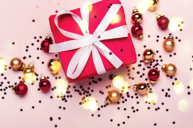 Christmas gift box and balls with confetti on pink background.