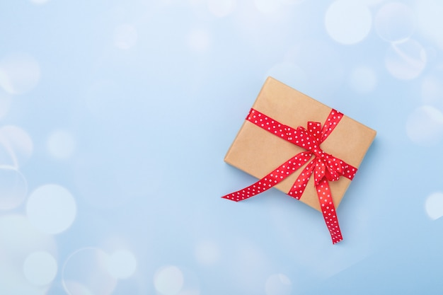 Christmas gift box and bokeh decoration on blue background