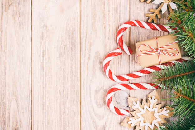Christmas gift box, candy cane with snowflake and fir tree branch on wooden table.