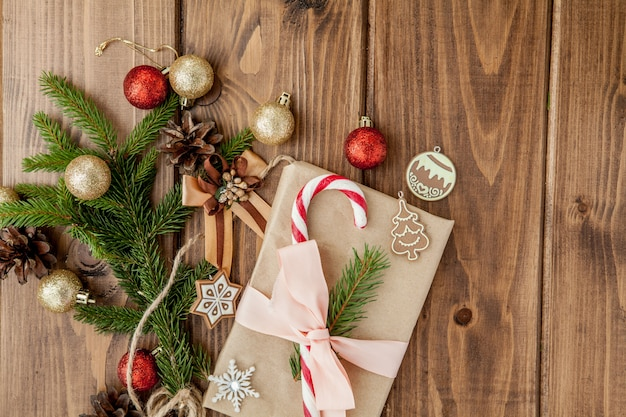 Christmas gift box, decor and fir tree branch on wooden table. top view with copyspace