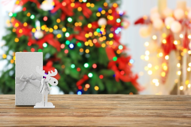 Christmas gift box and decorative deer on wooden table
