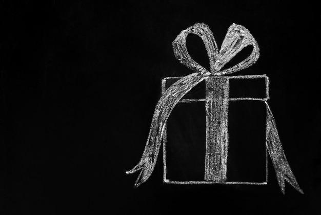 Christmas . gift box drawn with white chalk on blackboard. copyspace.