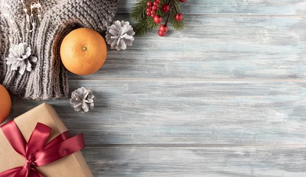 クリスマスのギフトボックス、食品の装飾、木製のテーブルの上のモミの木の枝。コピースペースのある上面図