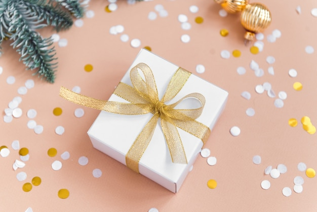 紙吹雪と装飾ボールとベージュの背景にクリスマスギフトボックスゴールデンカラーリボン