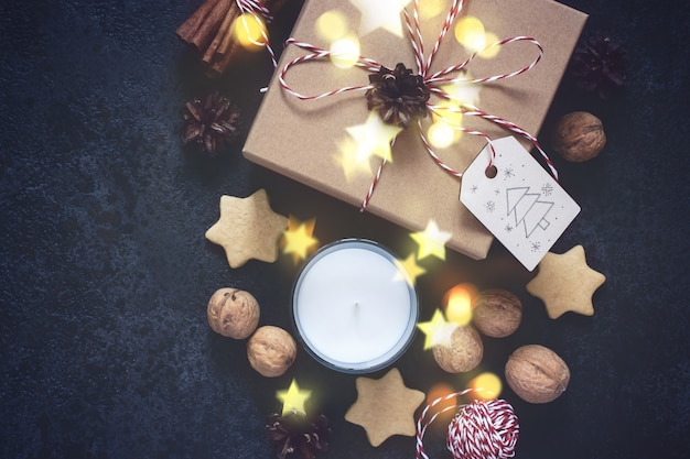 Christmas gift box and holiday decorations on black background