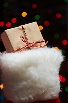 後ろにカラフルなボケライトが付いたクリスマスソックスのクリスマスギフトボックス