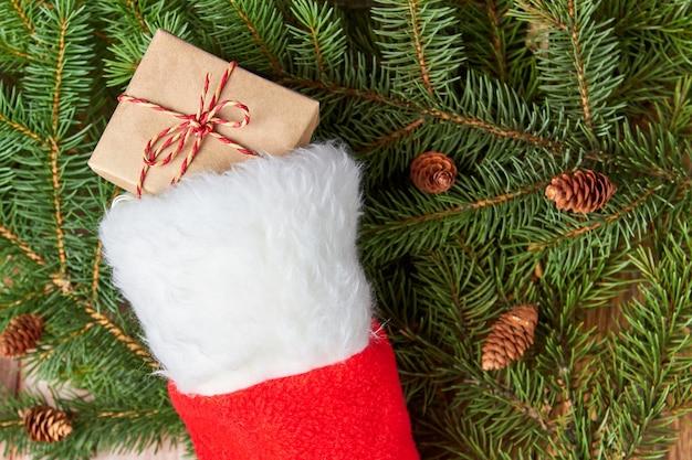 モミの枝の上のクリスマス靴下のクリスマスギフトボックス