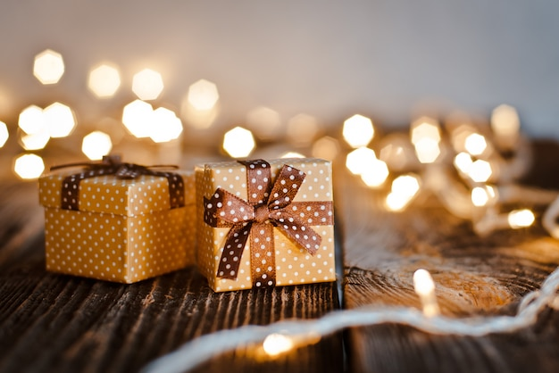 Christmas gift box lay on a wooden table on a bokeh of festive lights.