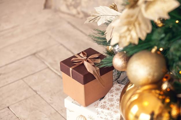 Новогодняя подарочная коробка лежит на полу под елкой, украшенной золотыми игрушками-шарами и гирляндами