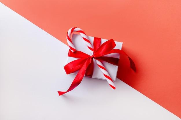 キャンディーとピンクと白のスペースにクリスマスギフトボックス。クリエイティブなミニマルコンポジション。