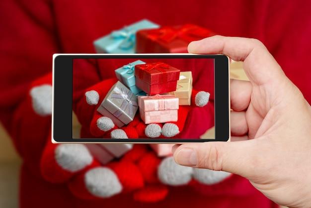 Рождественская подарочная коробка на экране смартфона.