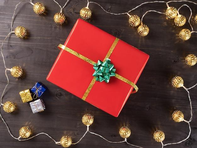 Рождественская подарочная коробка на деревянном фоне с небольшими подарками и рождественским светом. счастливых зимних праздников.