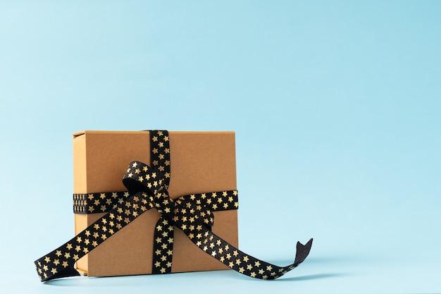 Рождественская подарочная коробка или подарочная коробка с черной золотой лентой на синем фоне