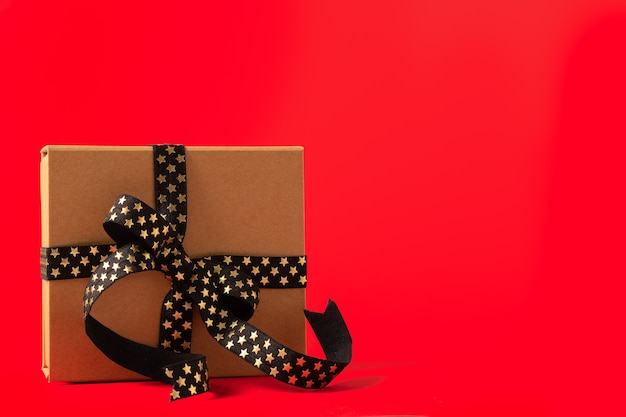 Рождественская подарочная коробка или подарочная коробка с черной золотой лентой на красном фоне.