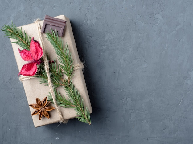 Christmas gift box in paper with winter spices on a gray concrete, copy space