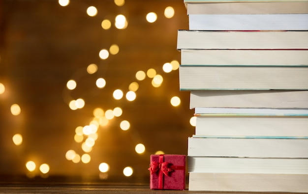 Christmas gift box and pile of books with fairy lights